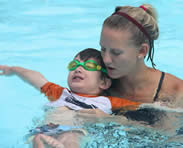 Woman helps child float in pool.